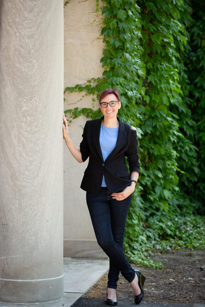Maggie Dull, wearing a blazer and blue shirt, standing next to a series of white and ivy covered columns at the University of Rochester.