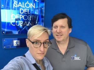 Maggie Dull and David Blake, standing in front of a sign for the Salon del Deportes Cubano in Havana, Cuba.